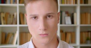 Close-upportret van jonge knappe Kaukasische mannelijke student die camera in de universiteitsbibliotheek bekijken stock video