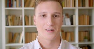 Close-upportret van jonge knappe Kaukasische mannelijke student die cheerfully het bekijken camera in de universiteitsbibliotheek stock footage