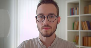 Close-upportret van jonge knappe Kaukasische mannelijke student die in oogglazen camera in de flat binnen bekijken stock video