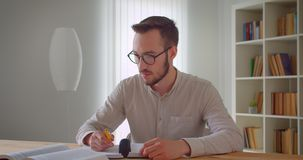 Close-upportret van jonge knappe Kaukasische mannelijke student in oogglazen die en de tablet in de universiteit bestuderen gebru stock video