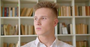 Close-upportret van jonge knappe Kaukasische student die camera in de universiteitsbibliotheek binnen bekijken stock footage