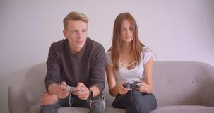 Close-upportret van jonge leuke Kaukasische gamerpaar het spelen videospelletjes die samen op de laag binnen in zitten stock videobeelden