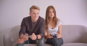 Close-upportret van jonge leuke Kaukasische paar het spelen videospelletjes die samen op de laag binnen in zitten stock footage