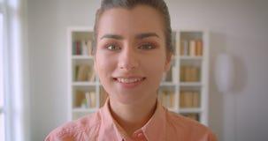 Close-upportret van jonge leuke vrouwelijke student die camera bekijken die in de universiteitsbibliotheek glimlachen stock footage