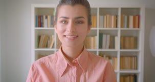 Close-upportret van jonge leuke vrouwelijke student die camera bekijken die gelukkig in de universiteitsbibliotheek glimlachen stock video