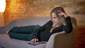Close-upportret van jonge mooie huisvrouw gebruikend de tablet en liggend op de bank binnen laidback bij comfortabel huis stock video