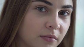Close-upportret van jonge mooie vrouw die met verschillende gekleurde ogen camera in de ochtend bekijken Gelukkige Kaukasisch stock footage