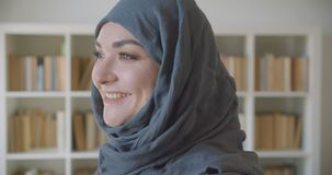 Close-upportret van jonge moslim aantrekkelijke onderneemster die in hijab camera bekijken die gelukkig in de bibliotheek glimlac stock footage