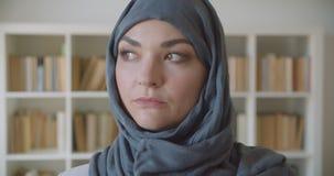 Close-upportret van jonge moslim aantrekkelijke onderneemster die in hijab vooruit in de bibliotheek binnen kijken stock footage