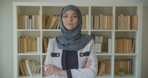 Close-upportret van jonge moslim aantrekkelijke vrouwelijke arts die in hijab camera in de bibliotheek binnen bekijken stock footage