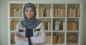 Close-upportret van jonge moslim aantrekkelijke vrouwelijke arts die in hijab en witte laag camera in de bibliotheek bekijken stock footage