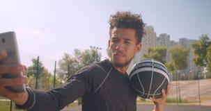 Close-upportret van jonge sportieve Afrikaanse Amerikaanse mannelijke basketbalspeler die een bal houden en selfies op de telefoo stock video