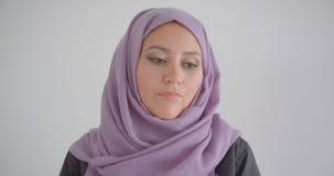 Close-upportret van jonge vrij Arabische vrouw die in die hijab camera met achtergrond bekijken in wit wordt geïsoleerd stock videobeelden