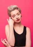 Close-upportret van jonge vrij blonde vrouw op roze achtergrond stock foto