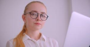 Close-upportret van jonge vrij Kaukasische blondeonderneemster in glazen die laptop met behulp van die cheerfully het kijken glim stock videobeelden