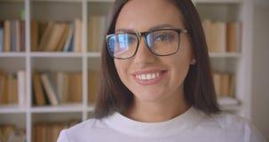 Close-upportret van jonge vrij Kaukasische onderneemster die in glazen camera bekijken die gelukkig binnen glimlachen met stock video