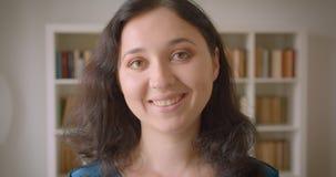 Close-upportret van jonge vrij Kaukasische vrouwelijke student die aan camera in de universiteitsbibliotheek binnen draaien met stock videobeelden