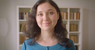 Close-upportret van jonge vrij Kaukasische vrouwelijke student die camera bekijken die cheerfully in de universiteitsbibliotheek  stock videobeelden