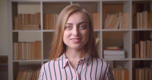Close-upportret van jonge vrij Kaukasische vrouwelijke student die camera bekijken die gelukkig in de universiteitsbibliotheek gl stock videobeelden