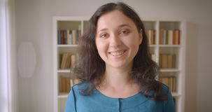 Close-upportret van jonge vrij Kaukasische vrouwelijke student die camera bekijken die gelukkig in de universiteitsbibliotheek gl stock video