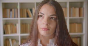 Close-upportret van jonge vrij Kaukasische vrouwelijke student die camera bekijken die nadenkend binnen in de bibliotheek zijn stock footage