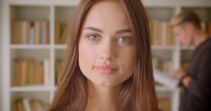 Close-upportret van jonge vrij Kaukasische vrouwelijke student die camera bekijken die zich in de bibliotheek met een jong mannet stock videobeelden