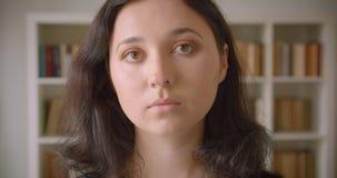 Close-upportret van jonge vrij Kaukasische vrouwelijke student die camera in de universiteitsbibliotheek binnen bekijken met stock videobeelden