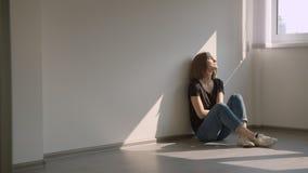 Close-upportret van jonge vrij Kaukasische vrouwelijke zitting op de vloer door het venster die gelukkig binnen in comfortabel gl stock footage