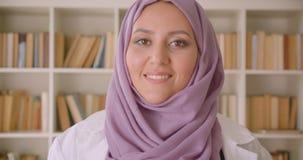 Close-upportret van jonge vrij moslim vrouwelijke arts die in hijab camera bekijken die gelukkig in bibliotheek glimlachen stock videobeelden