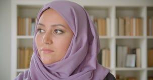 Close-upportret van jonge vrij moslim vrouwelijke student die in hijab camera bekijken die cheerfully in bibliotheek binnen gliml stock video