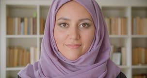 Close-upportret van jonge vrij moslim vrouwelijke student die in hijab camera bekijken die gelukkig in bibliotheek glimlachen stock video