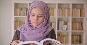 Close-upportret van jonge vrij moslim vrouwelijke student die in hijab een boek lezen die camera in de bibliotheek bekijken stock footage