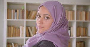 Close-upportret van jonge vrij moslim vrouwelijke student in hijab die en camera in bibliotheek draaien bekijken stock video