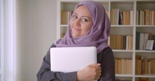 Close-upportret van jonge vrij moslim vrouwelijke student in hijab die laptop houden bekijkend camera die gelukkig binnen glimlac stock video