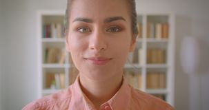 Close-upportret van jonge vrij vrouwelijke student die camera bekijken die cheerfully in de universiteitsbibliotheek glimlachen stock video