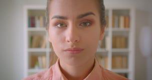 Close-upportret van jonge vrij vrouwelijke student die camera bekijken die gelukkig in de universiteitsbibliotheek glimlachen stock footage