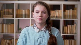 Close-upportret van jonge vrij vrouwelijke student die camera in de universitaire bibliotheek binnen bekijken stock videobeelden