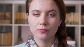 Close-upportret van jonge vrij vrouwelijke student die camera in de universitaire bibliotheek binnen met boekenrekken bekijken  stock videobeelden