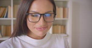 Close-upportret van jonge vrij zekere onderneemster die in glazen camera bekijken die gelukkig binnen glimlachen met stock videobeelden