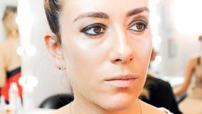 Close-upportret van jonge vrouw 30 jaar oud met bruine ogen die in schoonheidssalon stellen Royalty-vrije Stock Foto