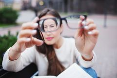 Close-upportret van jonge vrouwen met glazen Zij heeft zichtproblemen en is loensend zijn ogen een klein beetje Het mooie meisje  royalty-vrije stock afbeeldingen