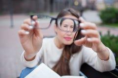 Close-upportret van jonge vrouwen met glazen Zij heeft zichtproblemen en is loensend zijn ogen een klein beetje Het mooie meisje  stock fotografie