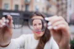 Close-upportret van jonge vrouwen met glazen Zij heeft zichtproblemen en is loensend zijn ogen een klein beetje Het mooie meisje  Stock Afbeelding