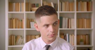 Close-upportret van jonge zekere aantrekkelijke zakenman die camera in bibliotheek binnen met boekenrekken bekijken  stock videobeelden