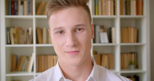Close-upportret van jonge zekere Kaukasische mannelijke student die cheerfully het bekijken camera in de universiteitsbibliotheek stock videobeelden