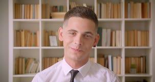 Close-upportret van jonge zekere zakenman die camera bekijken die gelukkig in bibliotheek binnen met boekenrekken glimlachen  stock video