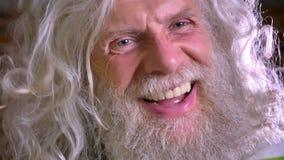 Close-upportret van Kaukasische oma, ontzagwekkend lang wit baard en haar, die gelukkig bij camera in motie, baksteen lachen stock video