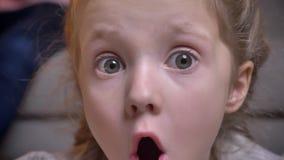 Close-upportret van klein Kaukasisch meisje met vlechten die haar vermaak tonen door haar mond in camera in comfortabel te openen stock video