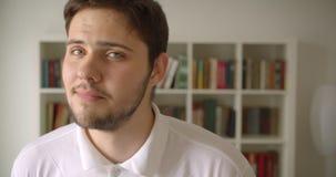 Close-upportret van knap Kaukasisch mannetje die camera in de bibliotheek met boekenrekken op de achtergrond bekijken stock footage