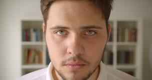 Close-upportret van knap Kaukasisch mannetje die recht camera in de bibliotheek met boekenrekken op de achtergrond bekijken stock video